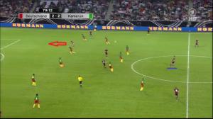 Müller wybiega (czerwona strzałka) do górnego podania Hummelsa (podkreślony niebieską linią) za linię obrony Kamerunu,